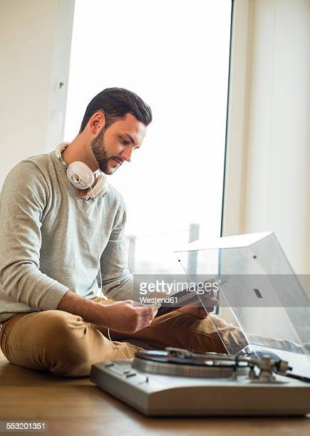 Young man at home looking at record and turntable