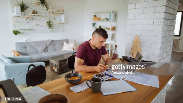 young man at home, paying bills online - home finances stock pictures, royalty-free photos & images