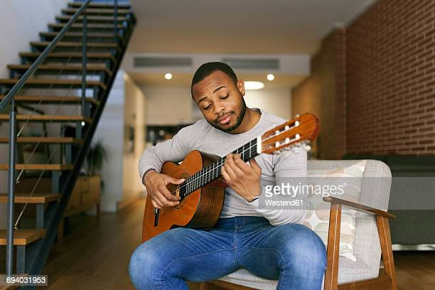 young man at home playing guitar - guitar stock pictures, royalty-free photos & images