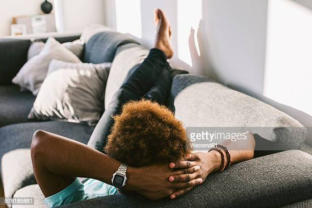 young man at home relaxing on couch - barefoot black men stock pictures, royalty-free photos & images