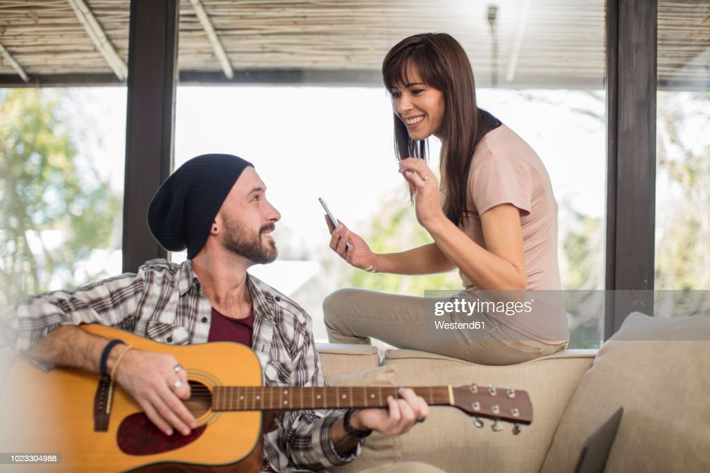 Young man at home sitting on couch playing guitar for woman : Stock Photo