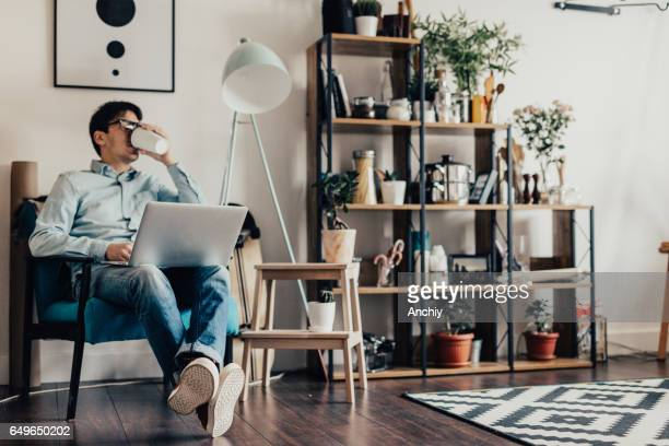 Jonge man thuis surft het internet en koffie drinken