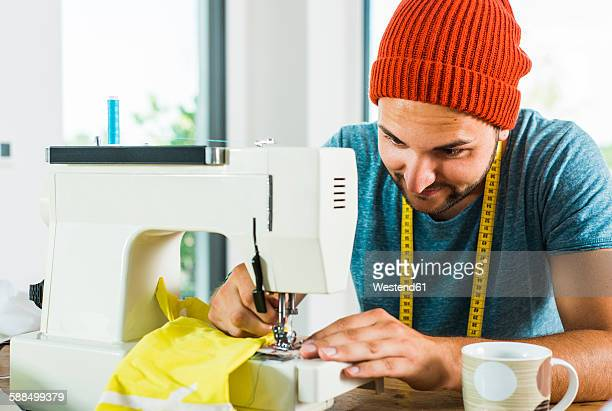 young man at home using sewing machine - sewing machine stock pictures, royalty-free photos & images