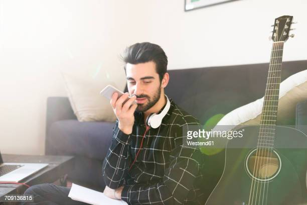 Young man at home with guitar using cell phone