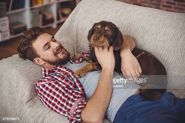 Young man at home with his dog.