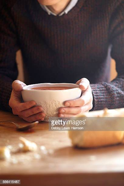 Young man at kitchen table with hands holding soup bowl