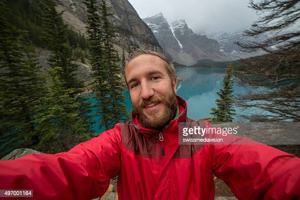 Young man at Moraine lake taking a selfie portrait