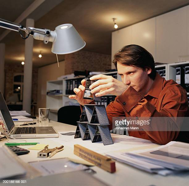 Young man at office desk, building house of cards