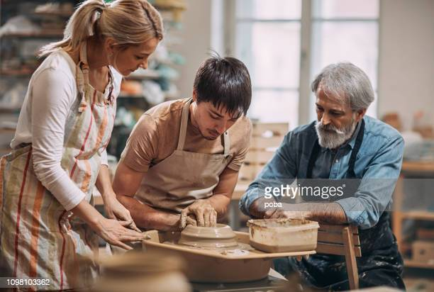 young man at  pottery workshop making clay pots - pottery stock pictures, royalty-free photos & images