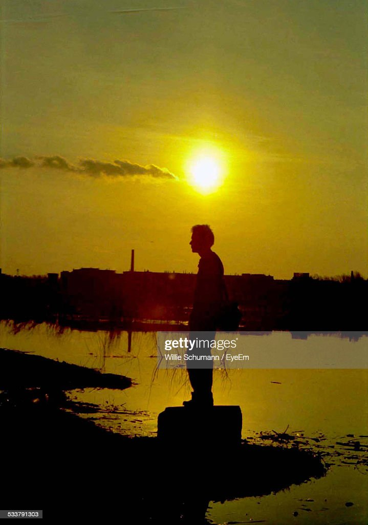 Young Man At Standing At Shore Of Lake Silhouetted Against Sunset : Foto stock