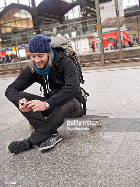 Young man at station checks cell phone