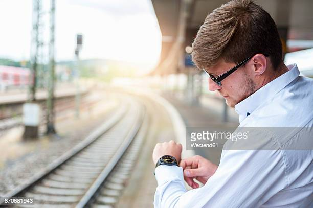 Young man at station platform checking the time