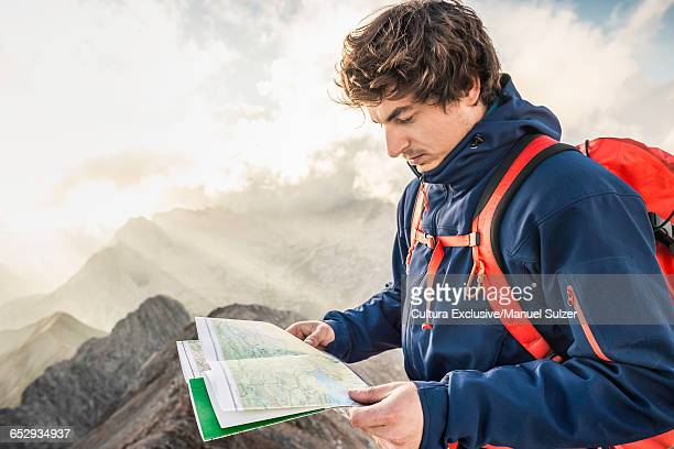 Young man at summit of mountain, looking at map, Mount Hochwanner, Wetterstein Mountains, Bavaria