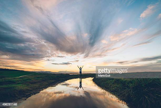 young man at sunset - motivatie stockfoto's en -beelden