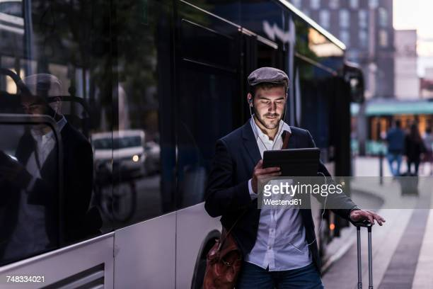 Young man at the bus stop in the city with earphones and tablet