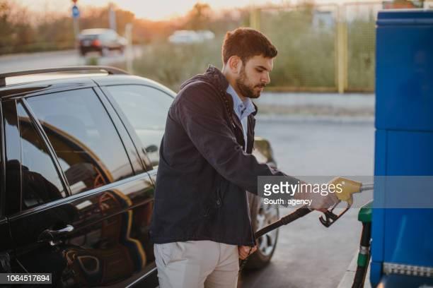 young man at the gas station - abastecer imagens e fotografias de stock