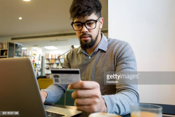 Young man at the library making credit card purchase online using laptop