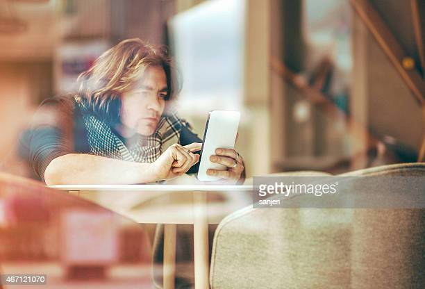 Young man at the restaurant with tablet computer