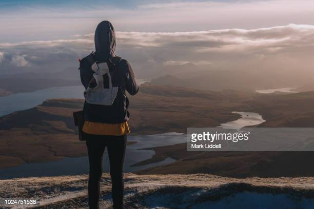 Young man at the summit of the Storr, overlooking Loch Leathan and Sound of Raasay, Isle of Skye