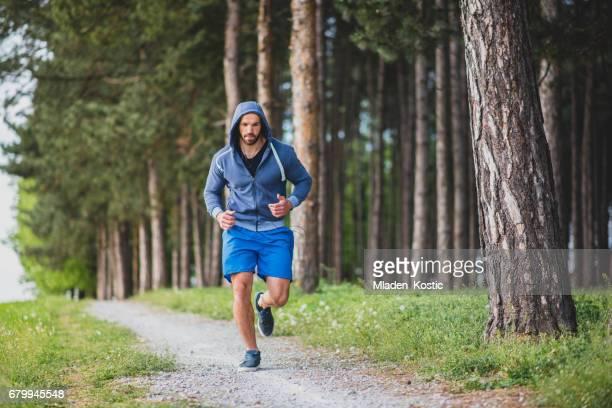 Junger Mann, Athlet läuft in den Wald