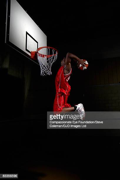 young man attempting to make a dunk - shooting baskets stock photos and pictures