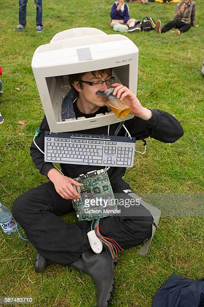 A young man attempts to dring his pint of beer through his broken computer screen as he participates in the fancy dress contest at the Standon...