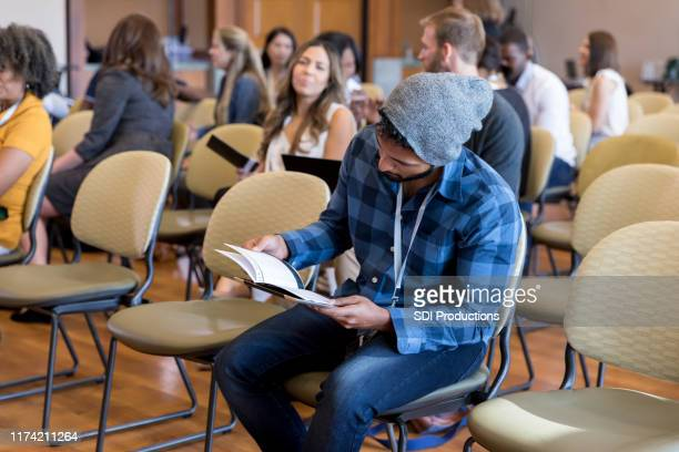 young man attends conference event - town hall meeting stock pictures, royalty-free photos & images