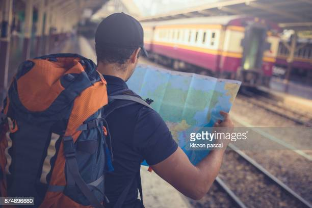 young man backpacker looking at the map while waiting for a train in railway station . - minderheit stock-fotos und bilder