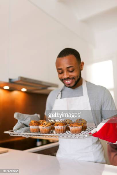 Young man baking cup cakes at home