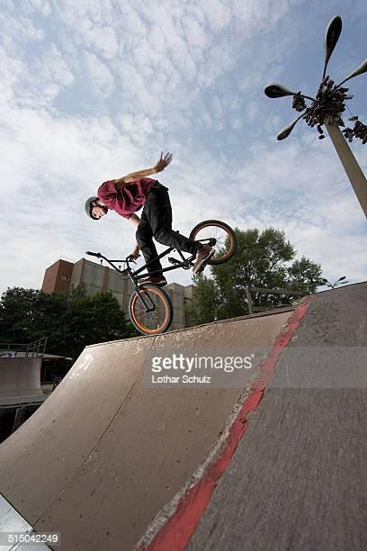 A young man balancing a BMX bike at the top of a ramp