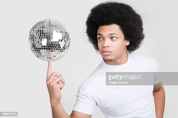 a young man balancing a disco ball - coiffure homme photos et images de collection