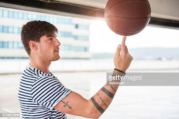Young man balancing basketball on finger