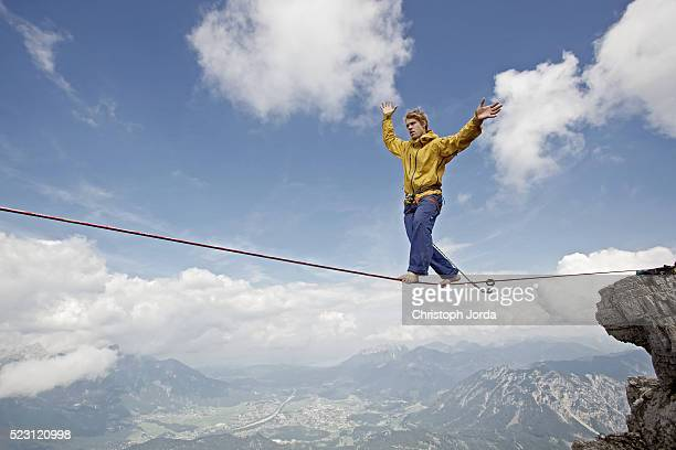 Young man balancing on high rope between two rocks in mountains, Alps, Tyrol, Austria
