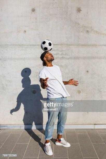 young man balancing soccer ball on his head in front of concrete wall - spielball stock-fotos und bilder