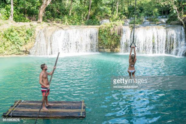 young man bamboo rafting and girl jumping from swing to tropical waterfall - bamboo stock photos and pictures