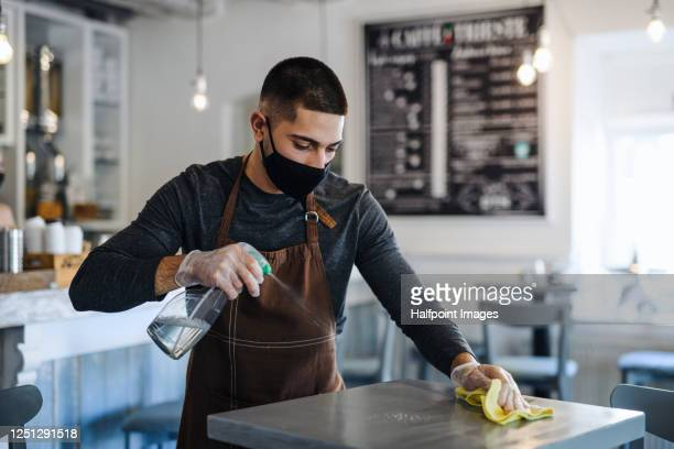 young man barista with face mask and gloves standing in coffee shop, disinfecting tables. - food service occupation stock pictures, royalty-free photos & images