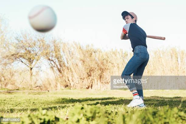 young man batting a baseball in park - batting sports activity stock pictures, royalty-free photos & images