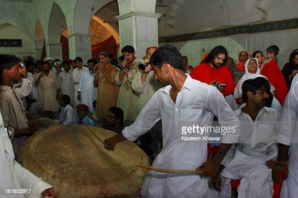 CONTENT] A young man beating traditional drums at the Shrine of Lal Shahbaz Qalandar on festival daysThis festival took place every year and...
