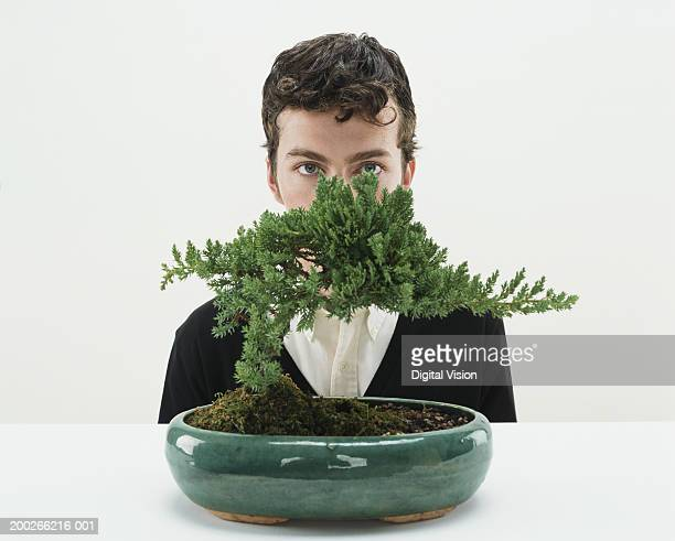 young man behind bonsai tree, portrait - bonsai tree stock pictures, royalty-free photos & images