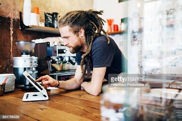 young man behind the counter of a café - só homens jovens imagens e fotografias de stock