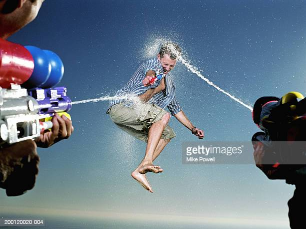 Young man being hit with water blast from two water guns