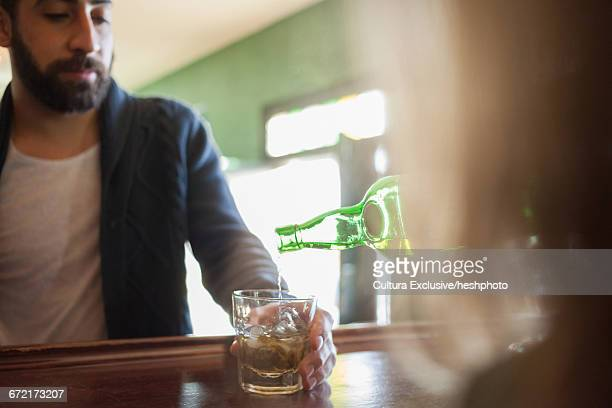 young man being poured whiskey in recreational bar - heshphoto stock pictures, royalty-free photos & images
