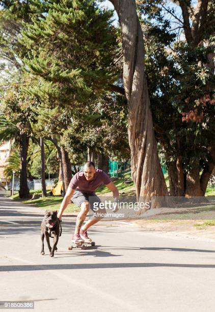 Young man being pulled on his skateboard by his dog at the park.