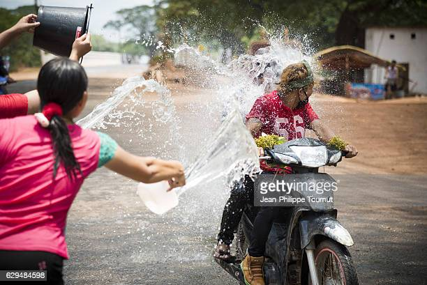 Young man being splashed by a bucket of water while riding a motorbike on the road during Thingyan Water Festival, Myanmar's traditional New Year Festival, in April 2016