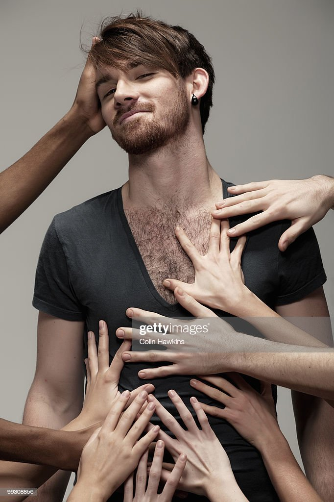 Young man being touched by hands : Stock Photo