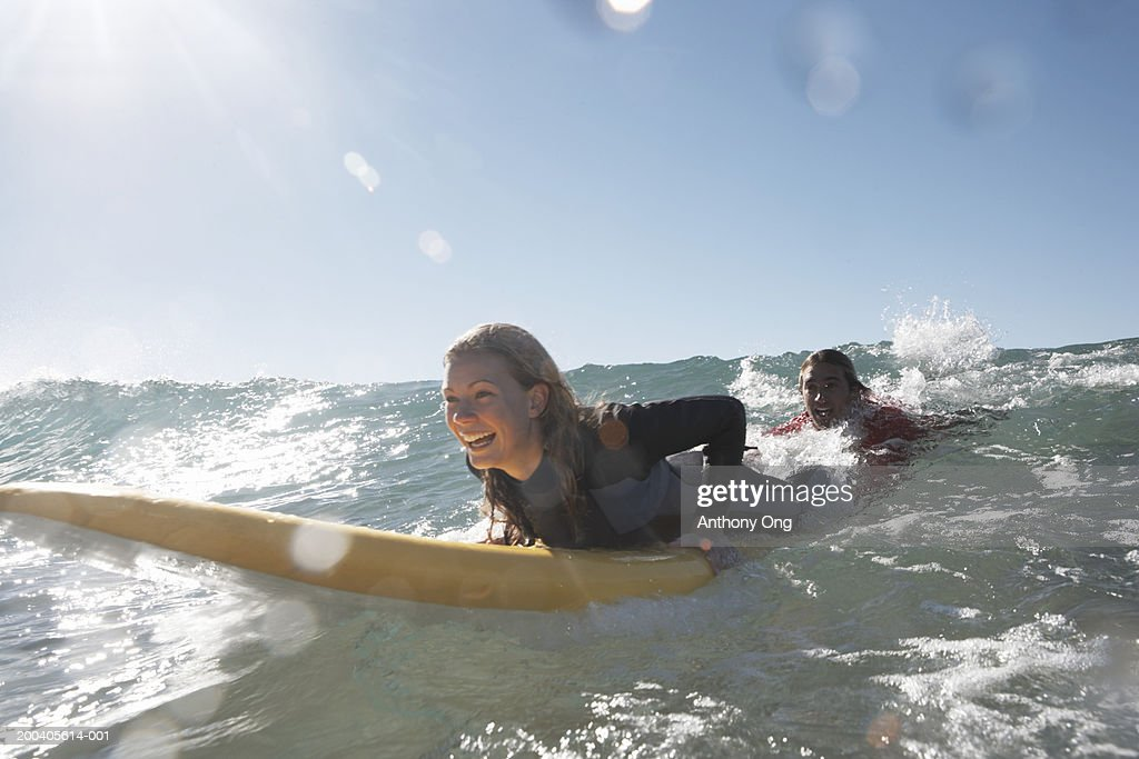 Young man being towed in sea by young woman on surfboard, smiling : Stock-Foto