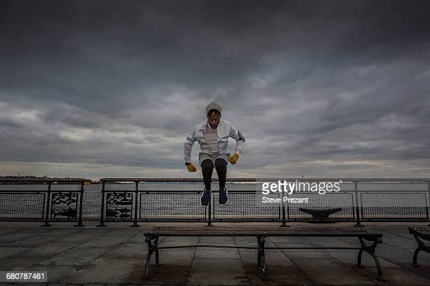 Young man bench jump training on riverside at dawn