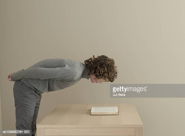 Young man bending and reading book