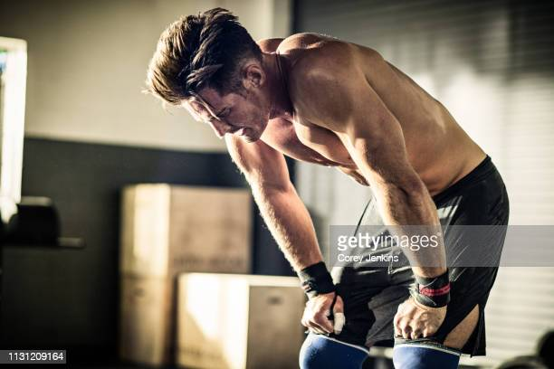 young man bending forward with exhaustion in gymnasium - musculoso fotografías e imágenes de stock