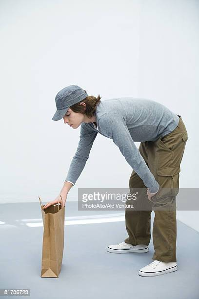 young man bending over, looking in paper shopping bag, side view - bending over stock pictures, royalty-free photos & images